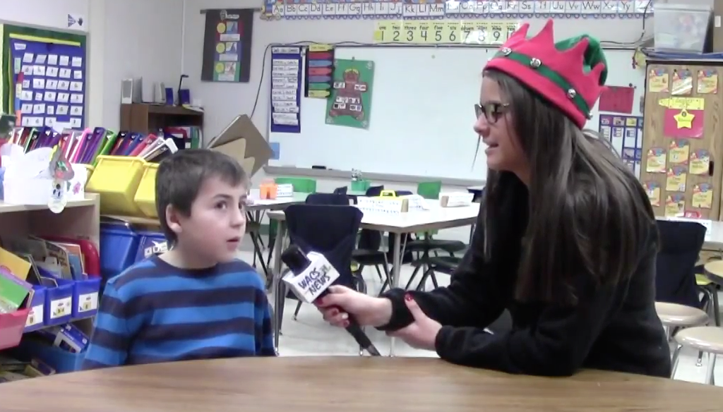 WACS News Reporter Morgan Rutan interviews a student about their gingerbread house project.